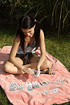She is playing baccarat on a blanket outdoor.