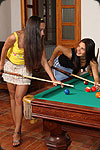 Two sexy girls in short skirts playing billiard.
