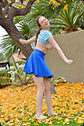 She is dancing on fallen yellow leaves outdoor.