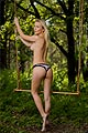 A topless blonde girl in panties stands barefoot near a swing in the woods.