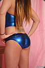 A teen go-go dancer wearing a shiny tight blue shorts.