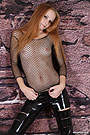 A hot girl posing wearing a black see-through fishnet T-shirt and no bra on.